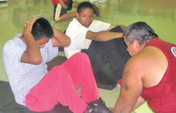 White Mountain Apache eighth grader Ryndell Caddo, 14, completes 25 situps while Martin Flores of Native Strong holds his feet during an assesment on Sept. 2 at Riverside Indian School in Anadarko, Okla.  NATIVE TIMES PHOTO BY DANA ATTOCKNIE